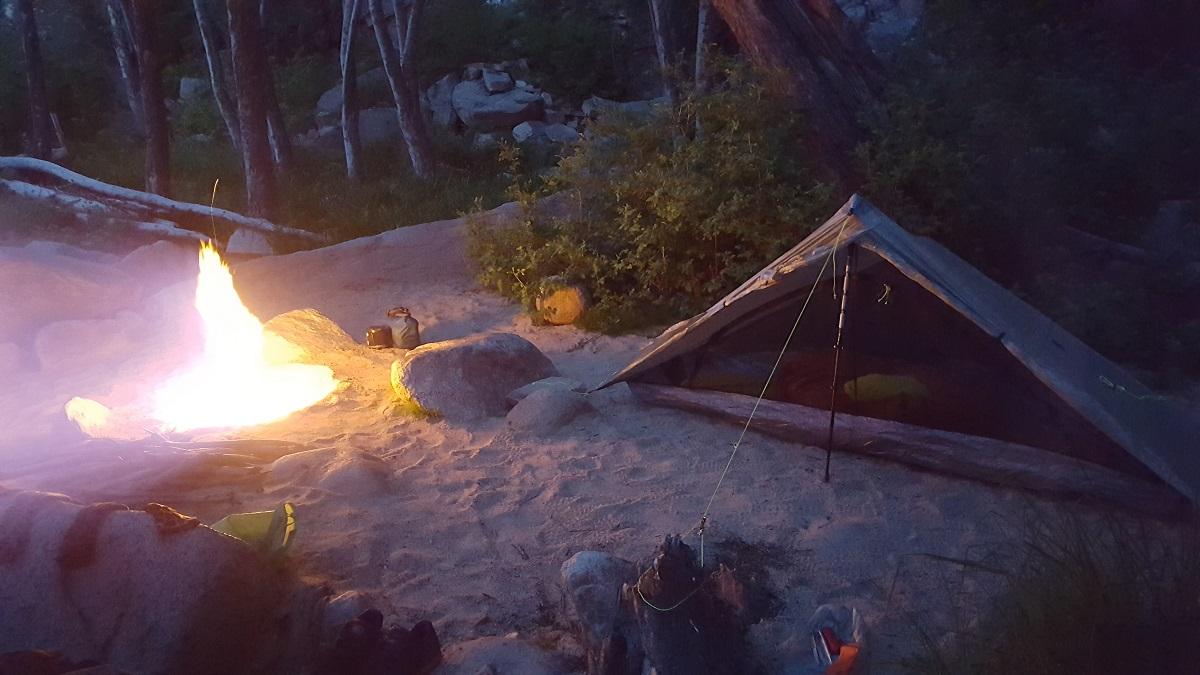 Campement dans le sable près d'une rivière