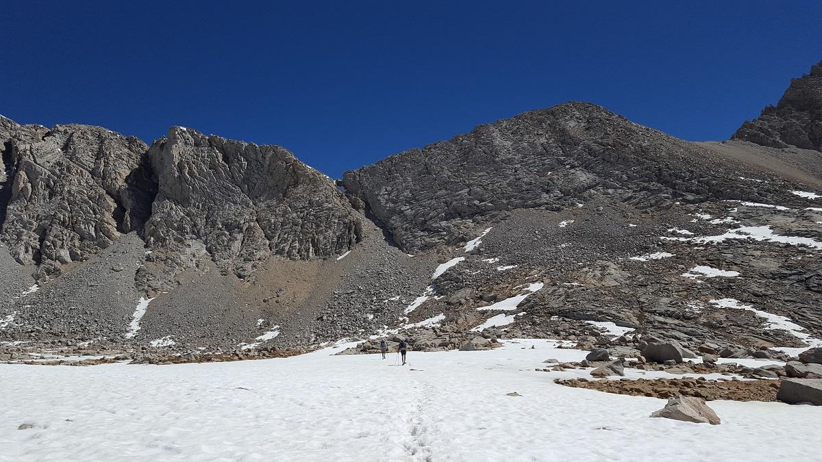 Champ de neige et pan de montagne gris et abrupte sur ciel bleu - Snow patch and steep grey mountain wall against blue sky