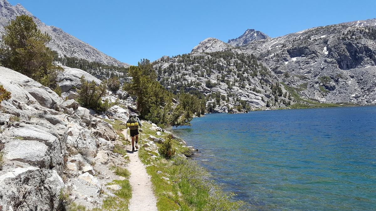 Marcheur sur le chemin qui longe un lac aux eaux bleur clair - Hiker on the trail by a light-blue lake